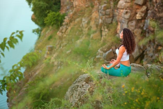 Junge frau praktiziert yoga in der nähe des flusses
