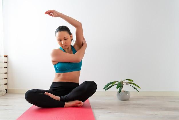 Junge frau praktiziert yoga zu hause, meditiert und sitzt auf einer matte. gegen die weiße wand.