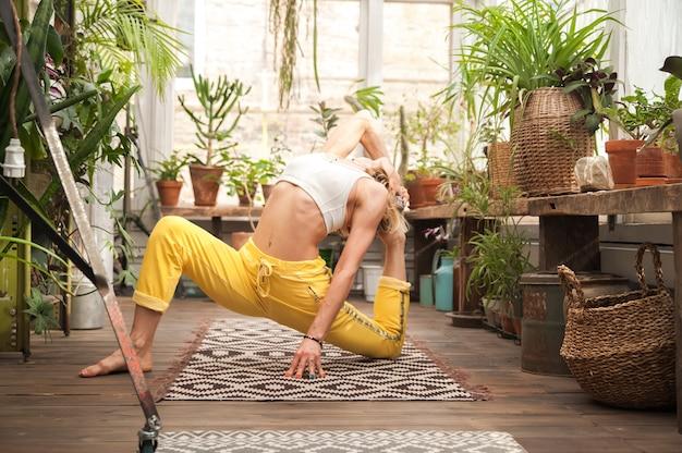 Junge frau praktiziert yoga zu hause unter blumen. städtischer dschungel und gymnastik, yoga, pilates.