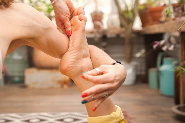 Junge frau praktiziert yoga zu hause unter blumen.