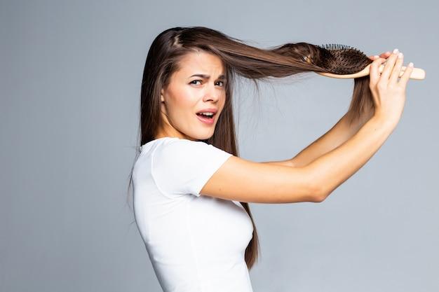 Junge frau probleme mit haaren, gespaltenes schwaches haar, verwirrtes haar isoliert auf grau