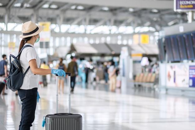Junge frau reisende, die gesichtsmaske und nitrilhandschuh hält griffgepäck im flughafenterminal, schutz coronavirus-krankheit (covid-19) -infektion trägt. neues normal- und reiseblasenkonzept