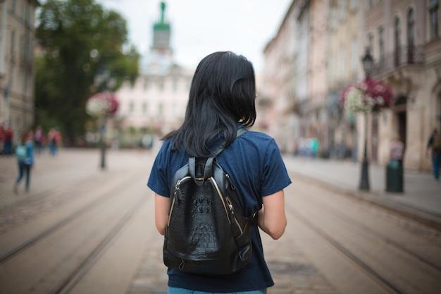 Junge frau reisende mit einem lederrucksack zu fuß in einer alten stadt lvov
