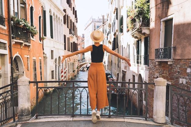 Junge frau reist durch italien. urlaub in europa. mädchen genießen schöne aussicht in venedig. weiblicher tourist, der auf straßen in venezia geht. modeblogger machen foto auf der malerischen brücke des canal grande.