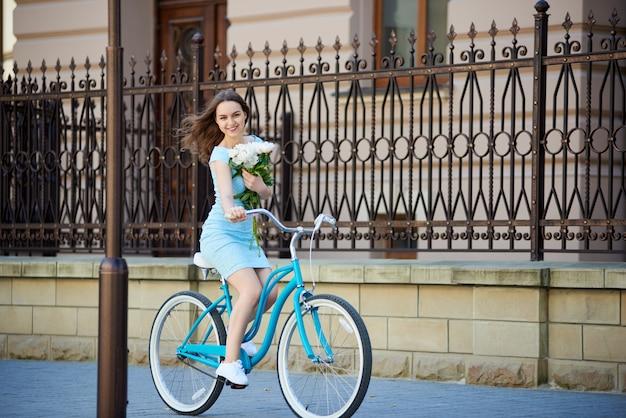 Junge frau reitet auf retro-fahrrad, das ihre pfingstrosen hält