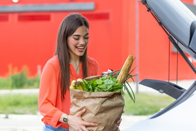 Junge frau reitet einkaufswagen voller lebensmittel auf dem außenparkplatz. junge frau im parkplatz, laden einkaufen in kofferraum des autos.