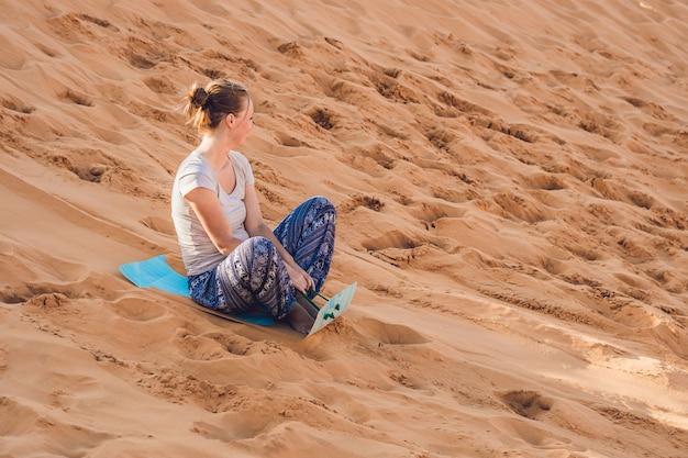 Junge frau rollt auf einer rodel im schlitten in der wüste.