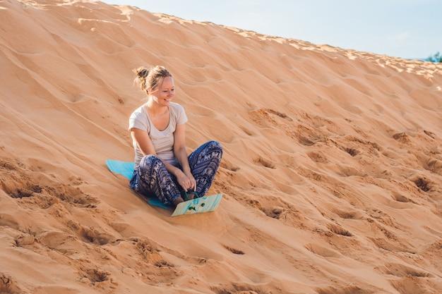 Junge frau rollt auf einer rodel im schlitten in der wüste