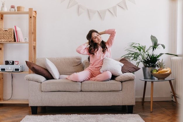 Junge frau ruht in ihrem zimmer, sitzt auf der couch, umgeben von bücherregalen und tisch mit blumentopf