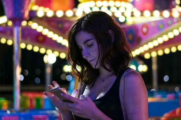 Junge frau schaut ihren smartphone in einer messe