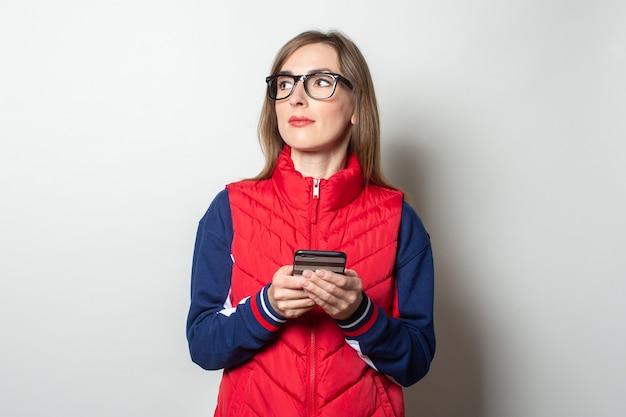 Junge frau schaut in einer roten weste zur seite und hält ihr handy in den händen gegen eine helle wand