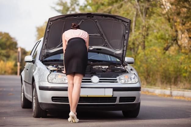 Junge frau schaut unter die motorhaube ihres autos und versucht, die ursache des bruchs zu finden