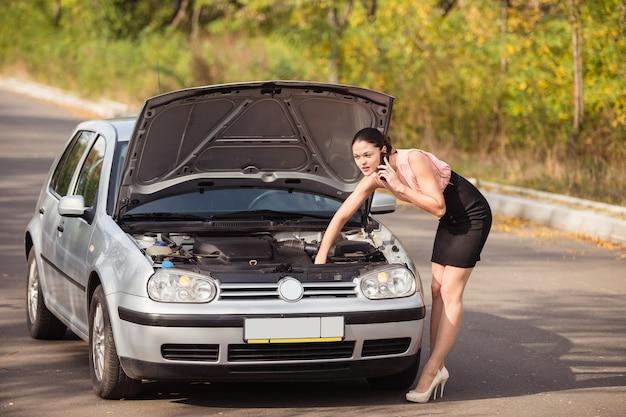 Junge frau schaut unter die motorhaube ihres autos und verursacht die evakuierung, weil ihr auto eine panne hat