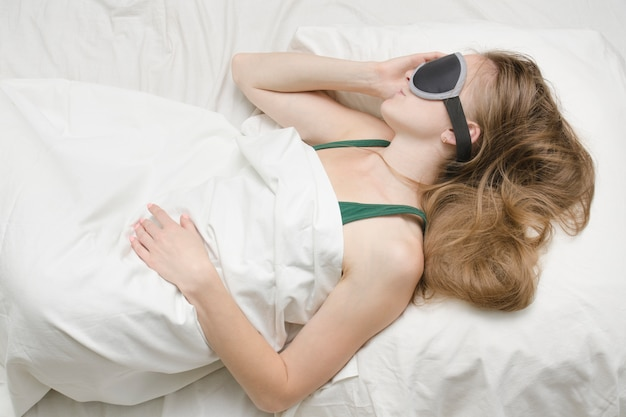 Junge frau schläft in einer maske zum schlafen