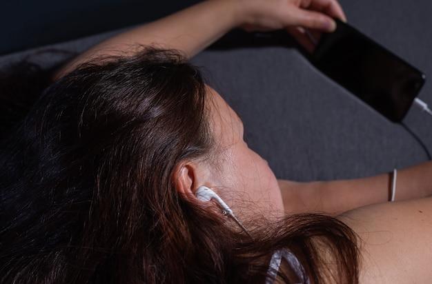 Junge frau schlief ein, während sie einen film auf ihrem smartphone sah und hörschäden hörte