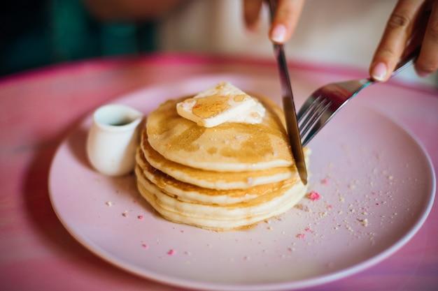 Junge frau schneidet stück vom stapel süßer pfannkuchen mit weichkäse oder butter, die in honig getränkt sind süße dessertskonzept der richtigen ernährung hausgemachtes essen desserts genießen