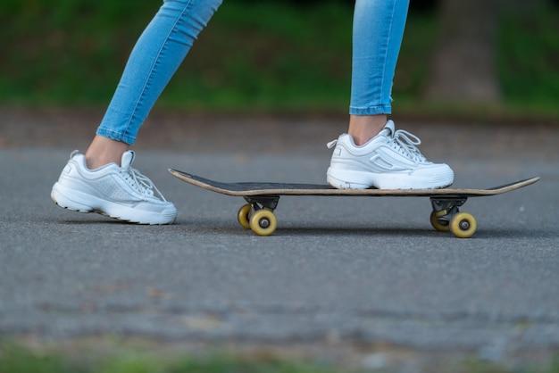 Junge frau schob sich auf einem skateboard in einem niedrigen blick auf ihre füße auf einer geteerten straße entlang