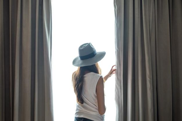 Junge frau schönheit tan asiatin mit hut offenen grauen vorhang auf weißem hintergrund