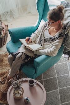 Junge frau schreibt im notizbuch, das im sessel am kamin sitzt
