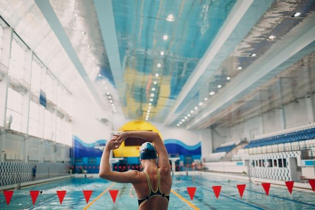 Junge frau schwimmer aufwärmen vor dem schwimmen im schwimmbad