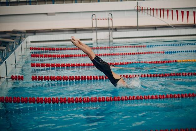 Junge frau schwimmerin im schwimmbad springen Premium Fotos