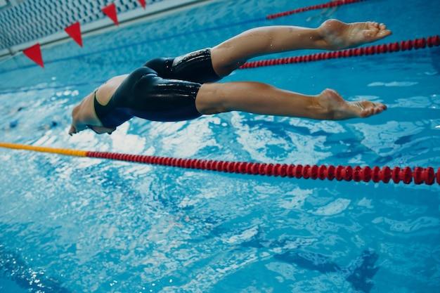 Junge frau schwimmerin im schwimmbad springen