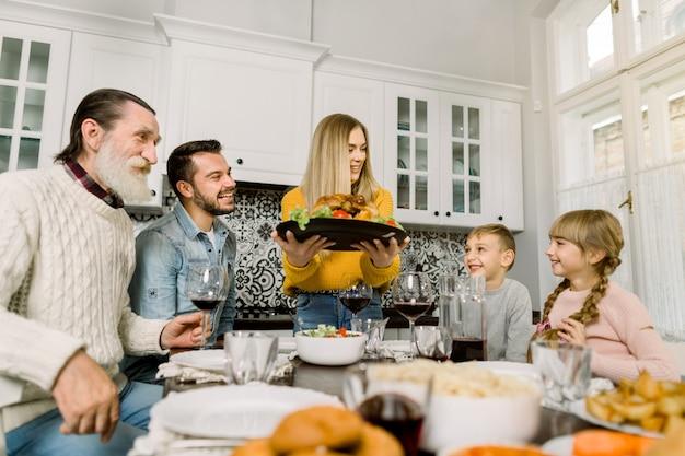 Junge frau serviert einen festlichen truthahn mit einem salat, großvater, vater und kinder sitzen und schauen sich das leckere essen an und lächeln