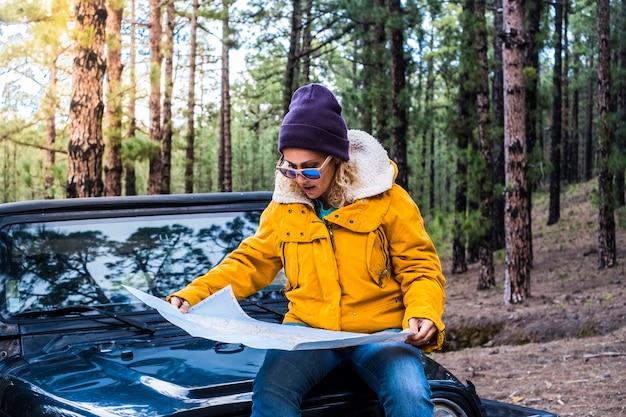Junge frau setzt sich auf das auto und überprüft den kartenführer im alleinreisen-abenteuer-lifestyle - weibliche menschen genießen wald- und naturwälder, die mit dem auto fahren und wilde orte erkunden