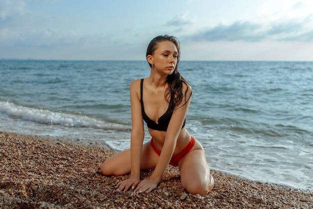Junge frau sexy sitzt auf den knien am strand