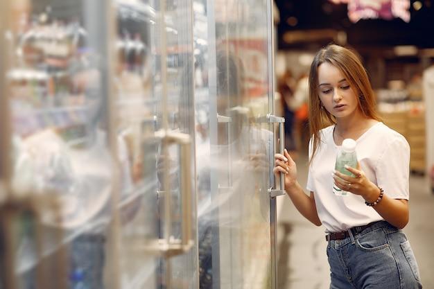 Junge frau shoppong im supermarkt