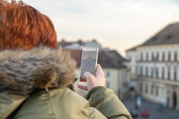 Junge frau sieht brünn von einer aussichtsterrasse aus an. fotografiere die stadt am telefon und teile sie auf der sozialen seite
