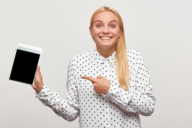 Junge frau sieht entzückt froh aus, erstaunt glücklich zahniges lächeln, tablette in der hand zeigt mit dem finger darauf