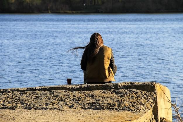 Junge frau sitzt allein auf dem pier mit kaffeetasse. rückansicht