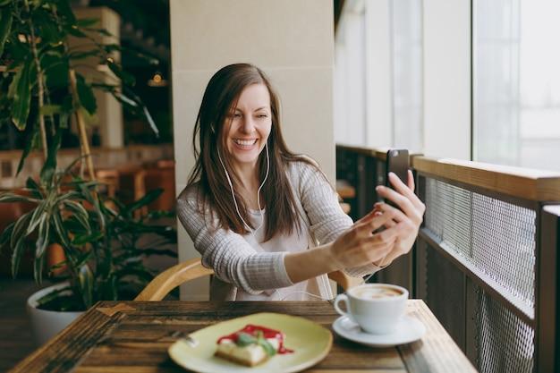 Junge frau sitzt allein im café am tisch mit einer tasse cappuccino, kuchen, entspannt sich in der freizeit im restaurant. junge frau macht selfie auf dem handy, ruht sich im café aus. lifestyle-konzept.