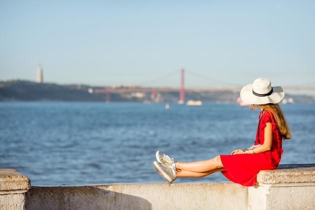 Junge frau sitzt am flussufer mit landschaftsblick auf der brücke in der stadt lissabon, portugal