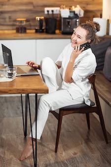 Junge frau sitzt am küchentisch mit einem laptop und spricht auf einem handy und lächelt. erfolgreiches mädchen, das zu hause lacht und arbeitet. schöne stilvolle frau, die zu hause lächelt und sich entspannt.