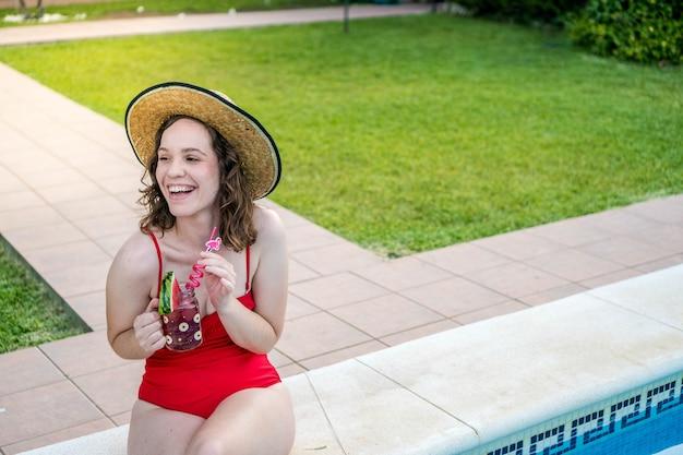 Junge frau sitzt am pool und trägt einen roten badeanzug frau trinkt im sommer einen cocktail
