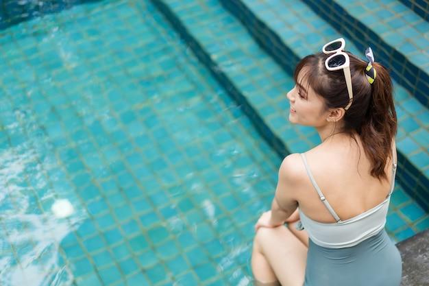 Junge frau sitzt am rand des schwimmbades