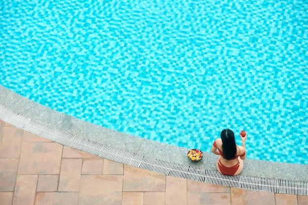 Junge frau sitzt am rand des swimmingpools, trinkt cocktail und isst frisches obst, blick von oben