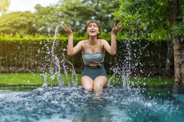 Junge frau sitzt am rand des swimmingpools und spielt wasserspritzer