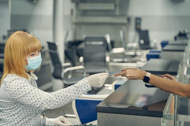 Junge frau sitzt an ihrem arbeitsplatz und kommuniziert mit passagieren vor dem flug