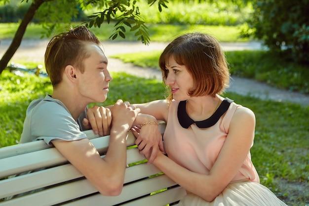Junge frau sitzt auf bank im öffentlichen park mit ihrem geliebten in der nähe während ihres treffens.