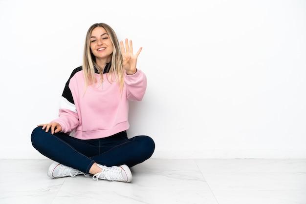 Junge frau sitzt auf dem boden im haus glücklich und zählt vier mit den fingern