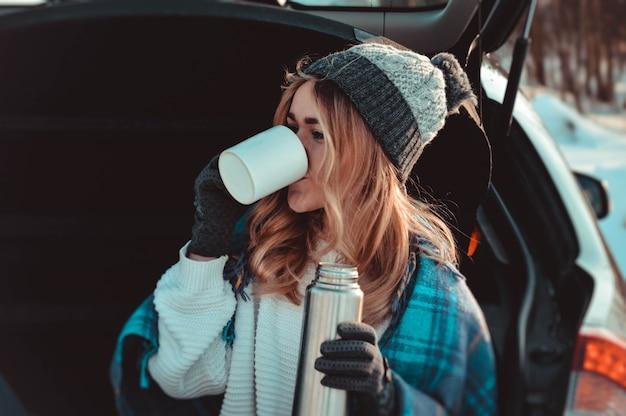 Junge frau sitzt auf dem kofferraum des autos mit kaffeetassen und thermoskanne im wintergebiet. warmer winterhintergrund. erwärmendes getränk.