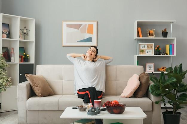 Junge frau sitzt auf dem sofa hinter dem couchtisch im wohnzimmer