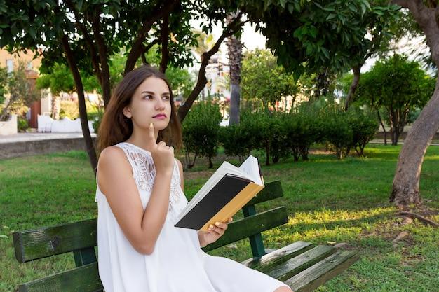 Junge frau sitzt auf der bank im park und denkt darüber nach, was sie gelesen hat