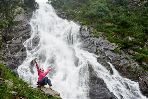Junge frau sitzt auf einem felsen mit ihren händen oben vor wasserfall