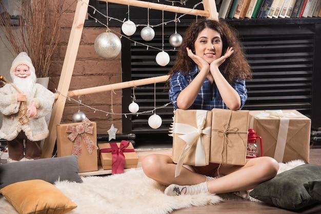 Junge frau sitzt auf einem flauschigen teppich mit kisten mit weihnachtsgeschenken
