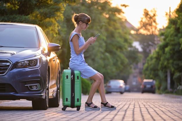 Junge frau sitzt auf einem koffer in der nähe ihres fahrzeugs und spricht im sommer mit ihrem handy auf einer stadtstraße.