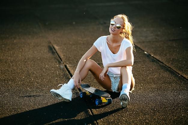Junge frau sitzt auf einem skateboard mit ihrer sonnenbrille an während des sonnenuntergangs.